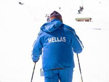 Man with ski and uniform with the name Hellas. Man skiing with the Hellenic colors snow jacket in a ski resort of Kalavrita Stock Photo
