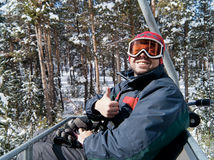Man skier on chairlift in forest. Happy man skier lift on chairlift in forest. Sarikamis, turkish ski resort Royalty Free Stock Photo