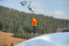 Man skier in flight during a jump over a hurdle. Male skier on his skis in flight during a jump over snowy slope from the mountain with forest in the distance on Stock Photo