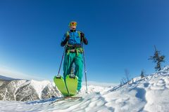 Man skier freerider standing at top of ridge, adventure winter freeride extreme sport.  Royalty Free Stock Image