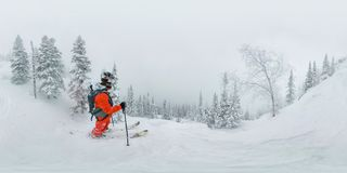 Man skier freerider standing at top of ridge, adventure winter freeride extreme sport stock photo