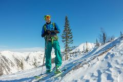 Man skier freerider standing at top of ridge, adventure winter freeride extreme sport.  Stock Photos