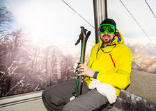 Man skier sit in ski lift cable car cabin. Man skier with beard and wearing ski mask sit in ski lift cable car cabin Stock Photos