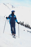 Man skier in ski suit stands looking down Stock Photos