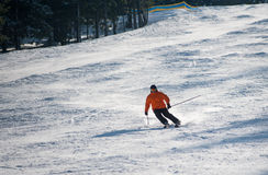 Man skier skiing downhill at ski resort. Male is wearing orange jacket, helmet and goggles Stock Images