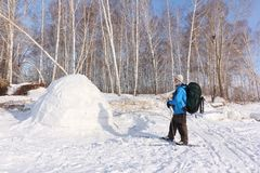 Man skier standing by an igloo on a glade. In the winter stock images