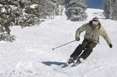Man Skiing Down Snow Covered Slope. Full length of a young man skiing down snow covered slope Stock Images