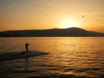 Sunset sky, mountain, sea and water skiing stock image