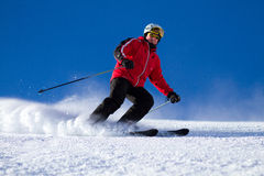 Man skiing on ski slope. Male skier skiing down steep ski slope. Trademarks have been removed Stock Photography
