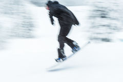A man skiing snow board very fast. blurred picture. Stock Image