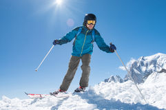 Man skiing on snow. Man skier running downhill on sunny Alps slope. Happy man in winter clothing skiing on mountain slope. Skier skiing in snowy mountain ski royalty free stock photo