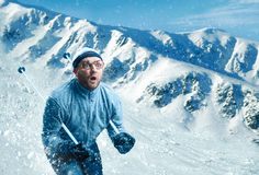 Man skiing. Surprised vintage skier in glasses skiing fast while snowing stock images