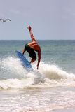 Man skimboarding. Rear view of bare chested young man on skimboard in sea royalty free stock images
