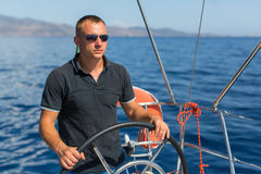 Man skipper at the helm sail boat Stock Photo