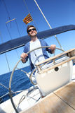 Man skipper navigating a sailing boat Stock Images