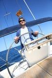 Man skipper navigating a sailing boat Stock Images