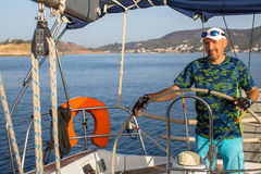 Man skipper steers boat sailing yacht on the Aegean Sea. Sport. Stock Photography
