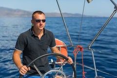 Man skipper steers sailing boat on the Sea. Royalty Free Stock Image