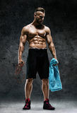 Man with skipping rope and towel in his hands. Resting time. Man with skipping rope and towel in his hands. Photo of sporty muscular man on dark background Royalty Free Stock Images