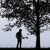 Man skogsarbetare med en yxa som står nära ett lövfällande träd i stock illustrationer
