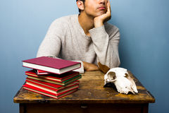 Man with skull and books is trying to think Stock Images