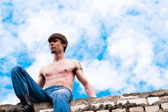 Man in the sky. A man sitting on a wall in the sky Stock Photos
