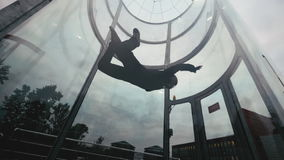Man skydiver flies in a circle in wind tunnel. Flying in a wind tunnel stock footage