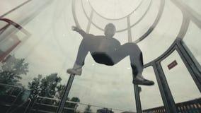 Man skydiver flies in wind tunnel. Indoor skydiving wind tunnel. Man skydiver flies in wind tunnel. Male skydiver training in wind tunnel. Paratrooper flies in stock video