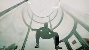Man skydiver skydiving in an indoor arena. Flying in a wind tunnel. Man skydiver skydiving in an indoor arena. Man skydiver spins in circular motion while going stock footage