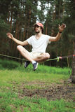 Man slacklining balancing on a rope, slackline in forest Royalty Free Stock Photos