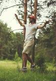 Man slacklining gå och att balansera på ett rep, slackline i skog Arkivbilder