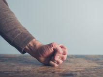 Man slamming his fist on table. Closeup on a man slamming his fist on a wooden table Royalty Free Stock Photo