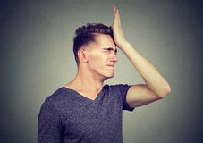 Man slapping hand on head having regrets. Isolated on gray background. Negative human emotion feeling Royalty Free Stock Photos
