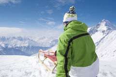 Man with sled on mountain top Royalty Free Stock Photo