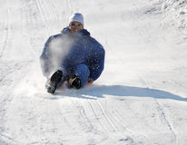 Man Sledding Down the Hill. Man sledding fast down the hill with snow background Stock Images