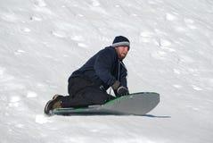 Man sledding down a snowhill Stock Photography