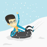 Man sledding on snow rubber tube in the mountains. Royalty Free Stock Photography