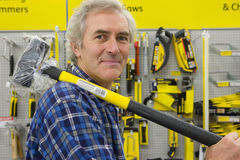 Man with sledge hammer in hardware store, portrait Royalty Free Stock Images