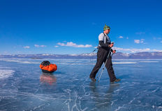Man with a sledge and trekking pole is on the ice of Lake Baikal Stock Photos