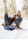 Man Sledging Through Snowy Woodland Royalty Free Stock Image