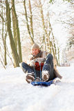 Man Sledging Through Snowy Woodland Royalty Free Stock Photography