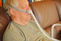 Senior man naps with CPAP device stock photo