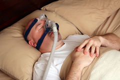 Man with sleep apnea using a CPAP machine stock photo