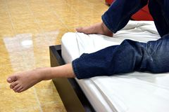 Man. Sleep on a bed wearing jeans, were seen only the legs and foot Royalty Free Stock Images
