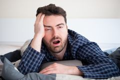 Man with sleep disorder lying in the bed. Man with sleep problem in his bed at home stock photography