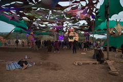 A man sleep on the ground while other people dance at the Lost Theory psytransce music festival held in Riomalo de Abajo