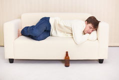 Man sleep on sofa having got drunk beer Royalty Free Stock Image