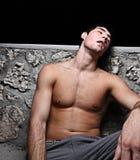 Man sleeping. Young homeless man sleeping on a wall Stock Image
