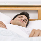 Man Sleeping. A man sleeping in bed.  Square framed shot Stock Image
