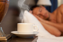 Man sleeping on abed, a cup of hot tea. Man sleeping on a bed, a cup of hot steaming coffee on the bedside table and lamp Stock Photography
